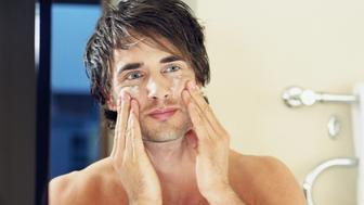 Bare chested young man applying face cream, reflection in mirror