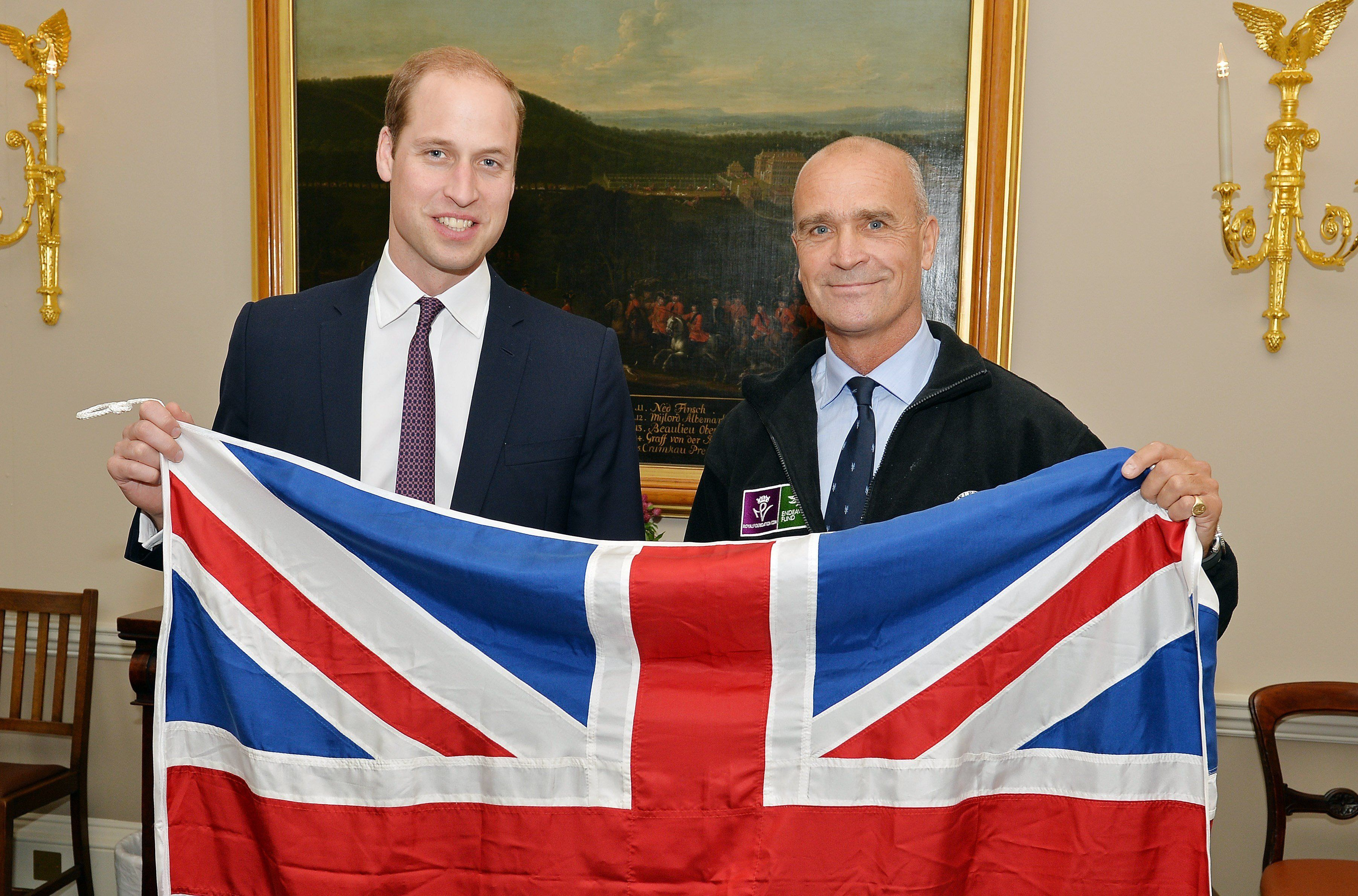 Britain's Prince William, Duke of Cambridge, (L) and polar explorer Henry Worsley, pose with a Union flag at Kensington Palace in London on October 19, 2015. Worsley will undertake the 2015/16 Shackleton solo challenge starting in November, and attempting to undertake Sir Ernest Shackleton's unfinished journey to the South Pole from the Weddell Sea.   AFP PHOTO / JOHN STILLWELL / POOL        (Photo credit should read JOHN STILLWELL/AFP/Getty Images)