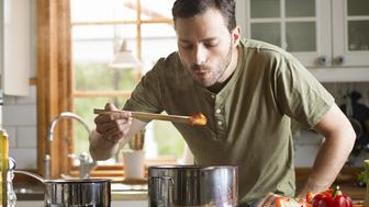 Man cooking, blowing on hot food on wooden spoon