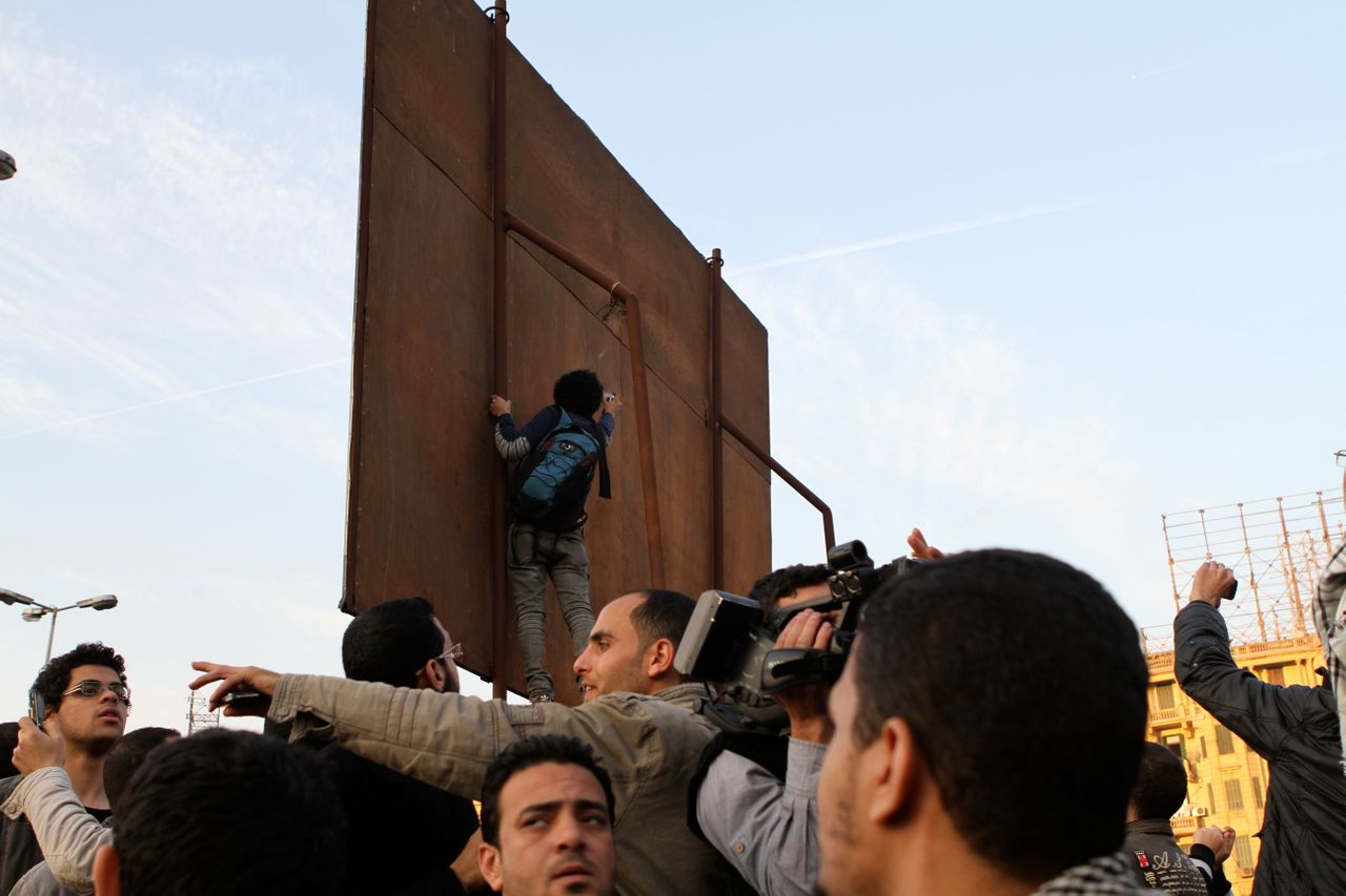Ganzeer's art played a public role during the 2011 protests in Tahrir Square. Here the artist can be seen at work above the crowd.