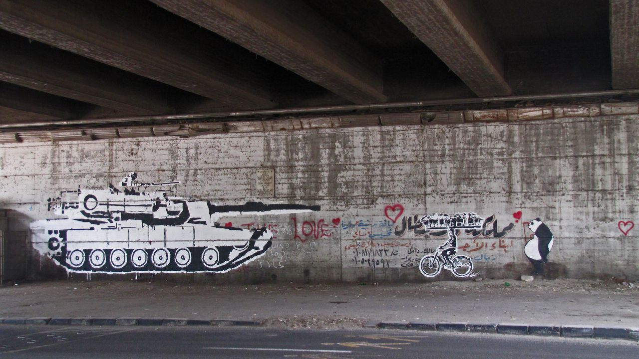 """""""Tank Vs Biker,"""" one of Ganzeer's first murals during the 2011 protests. The artist wanted to """"create awareness about the malpractices of Egypt's Supreme Council of the Armed Forces,"""" he said."""