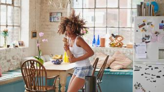 Happy curly haired  girl dancing in kitchen wildly hair bouncing wearing pyjamas at home photos on fridge