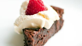 Gluten free flour-less chocolate cake served with whipped cream and raspberry topping.