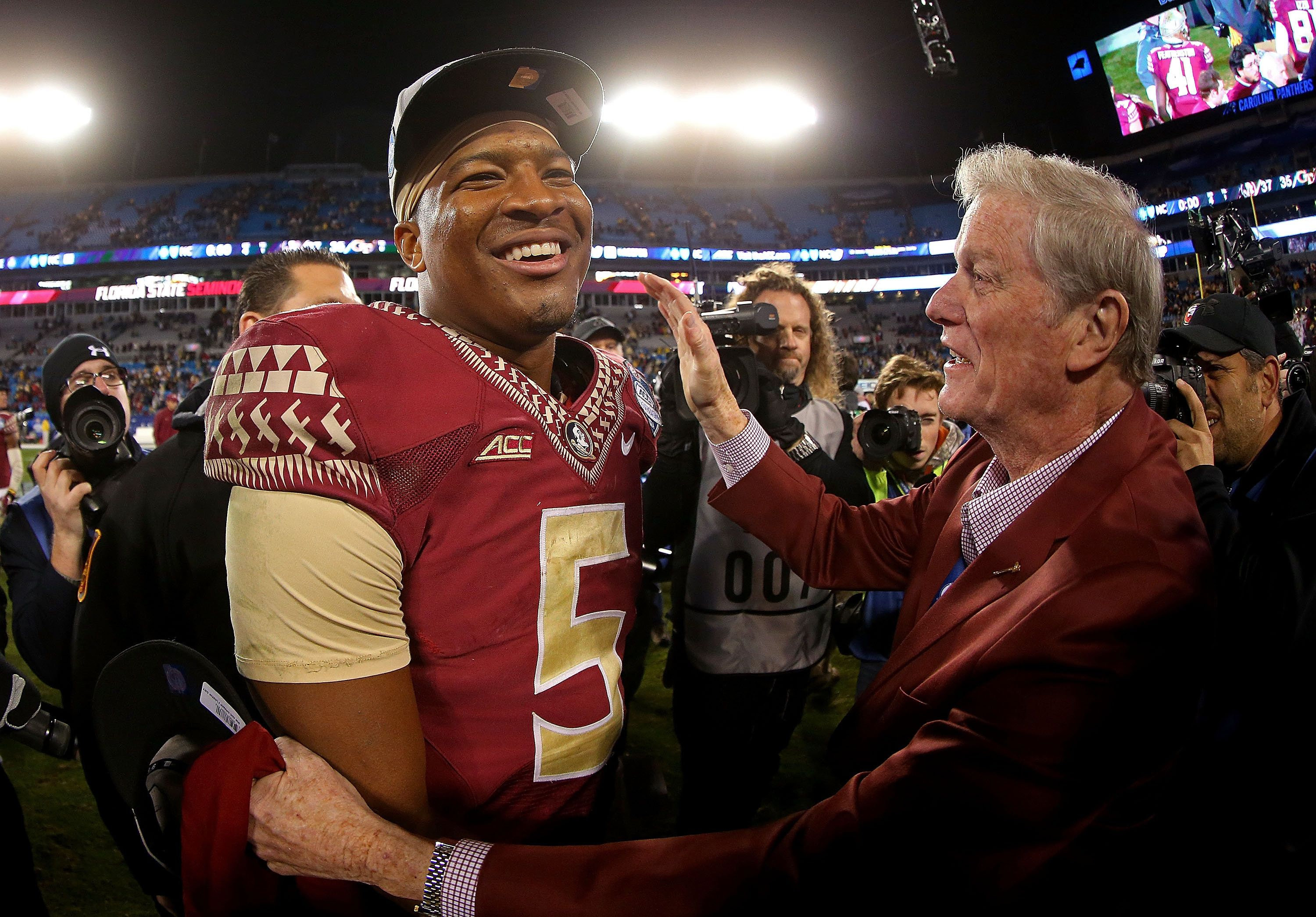 CHARLOTTE, NC - DECEMBER 06: Jameis Winston #5 of the Florida State Seminoles and university presiden John Thrasher congratulate each other after their 37-35 victory over the Georgia Tech Yellow Jackets at the ACC Championship game on December 6, 2014 in Charlotte, North Carolina.  (Photo by Mike Ehrmann/Getty Images)
