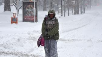 A homeless walks on snow covered 14th street North West in Washington on January 23, 2016. A deadly blizzard with bone-chilling winds and potentially record-breaking snowfall slammed the eastern US on Saturday, as officials urged millions in the storm's path to seek shelter -- warning the worst is yet to come. US news reports said at least eight people had died by late Friday from causes related to the monster snowstorm, which is expected to last until early Sunday.   / AFP / Mladen ANTONOV        (Photo credit should read MLADEN ANTONOV/AFP/Getty Images)