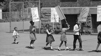 """Prentice Sharpe, 2 years old, fell into line behind the """"big kids"""" as they picketed a predominantly black elementary school in Albany, New York, May 18, 1964. It was part of an organized civil rights demonstration in several communities across New York State in observance of the 10th anniversary of the Supreme Court decision barring segregation in public schools. (AP Photo/Arthur Z. Brooks)"""