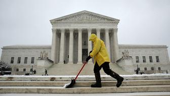 WASHINGTON, DC - MARCH 05:  A government employee shovels newly fallen snow from the steps of the U.S. Supreme Court March 5, 2015 in Washington, DC. The Washington DC area is expected to receive 4-8 inches of snow during the day.  (Photo by Win McNamee/Getty Images)