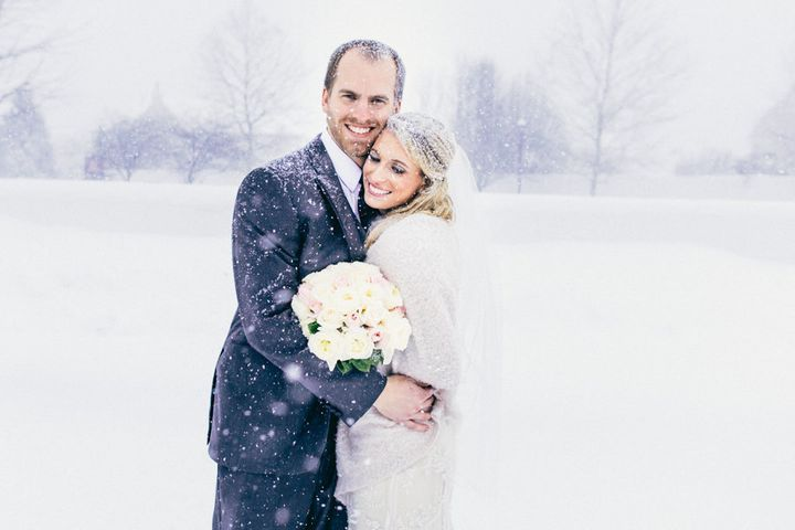 The bride and groom sharing a sweet, snowy embrace.