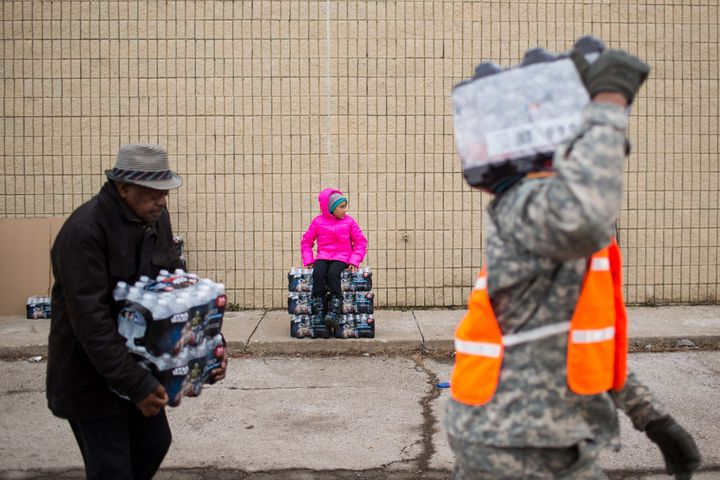 National Guard members and civilians carry cases of water to residents in Flint, Michigan, on Jan. 23.