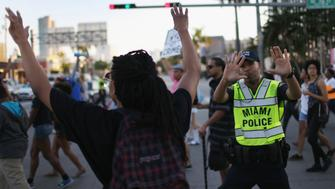 MIAMI, FL - DECEMBER 07: A City of Miami police officer stops traffic as demonstrators march through the Wynwood neighborhood to protest police abuse on December 7, 2014 in Miami, Florida. The protest was one of many that have take place nationwide after grand juries investigating the deaths of Michal Brown in Ferguson, Missouri and Eric Garner in New York failed to indict the police officers involved in both incidents (Photo by Joe Raedle/Getty Images)