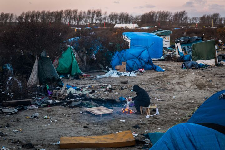 """A refugee sits in front of a fire in the refugee camp known as """"the Jungle"""" on Jan. 15, 2015 in Calais, France."""