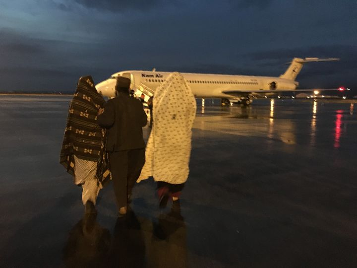 Reza Gul, her brother-in-law, mother, and baby sister walk towards the plane that will transport them to Kabul on Thursday. I
