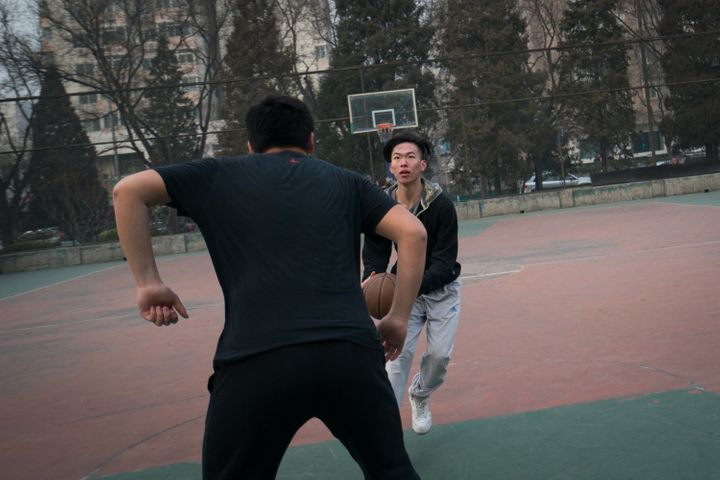 Frank plays basketball with friends near his home in Beijing.