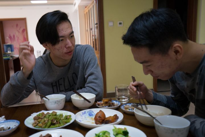 Frank and Richard eatlunch at their Beijing home.