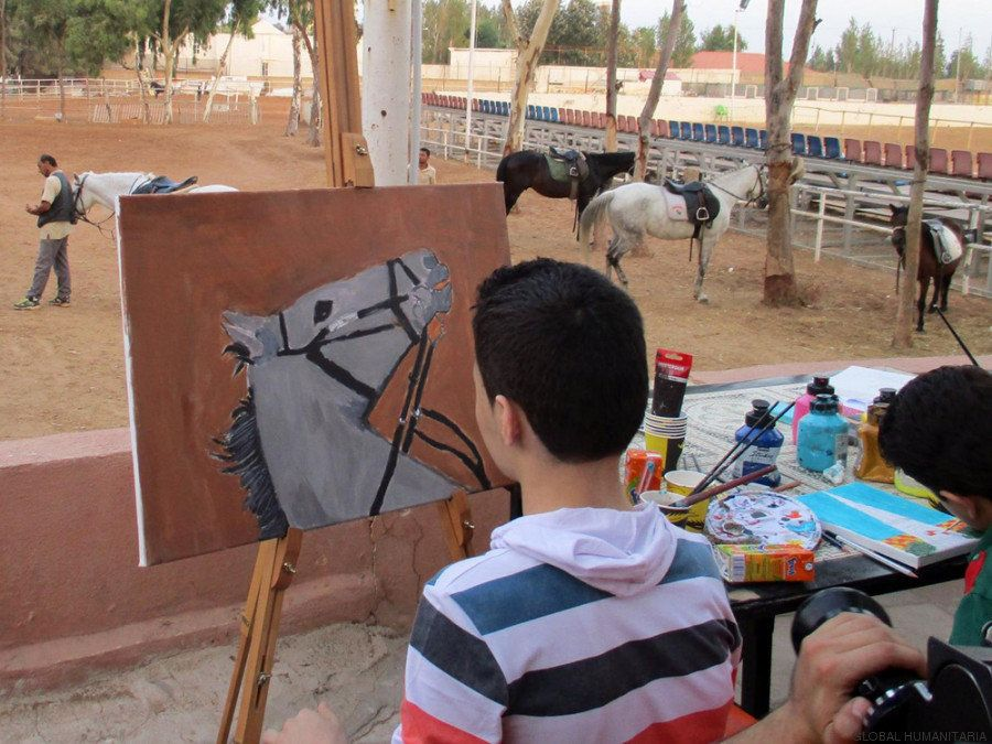 Wissam, a 14-year-old refugee living at the Bader Center, works on one of his paintings.