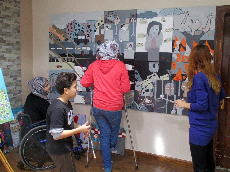Khaled, a 14-year-old refugee, and three young women are seen at the Bader Center's art workshop.