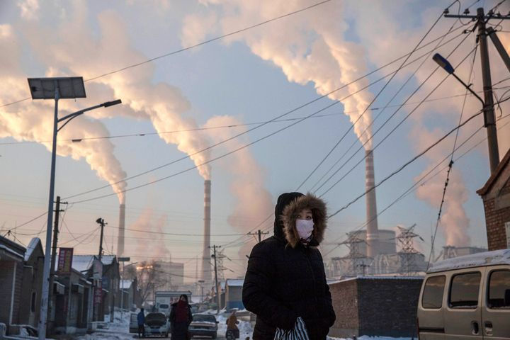 A woman wears as mask while walking in a neighborhood next to a coal-fired power plant on Nov. 26, 2015, in Shanxi, Chin