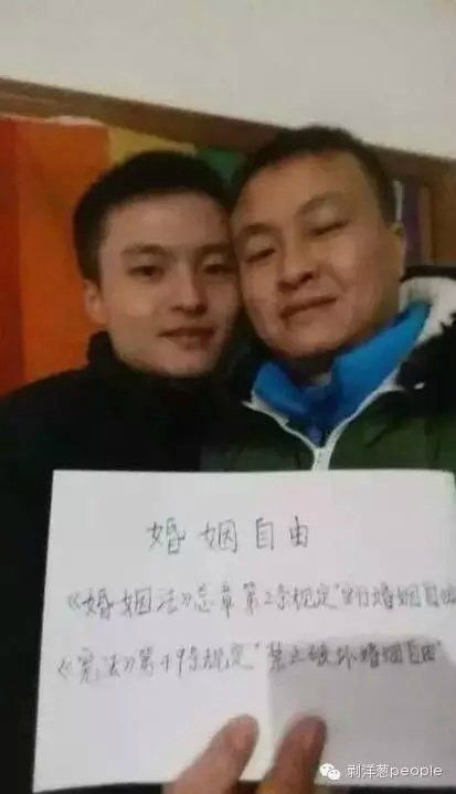 """Sun Wenlin, pictured here with his partner Hu Mingliang, holds a piece of paper that reads""""Marriage Freedom."""" Sun sued"""