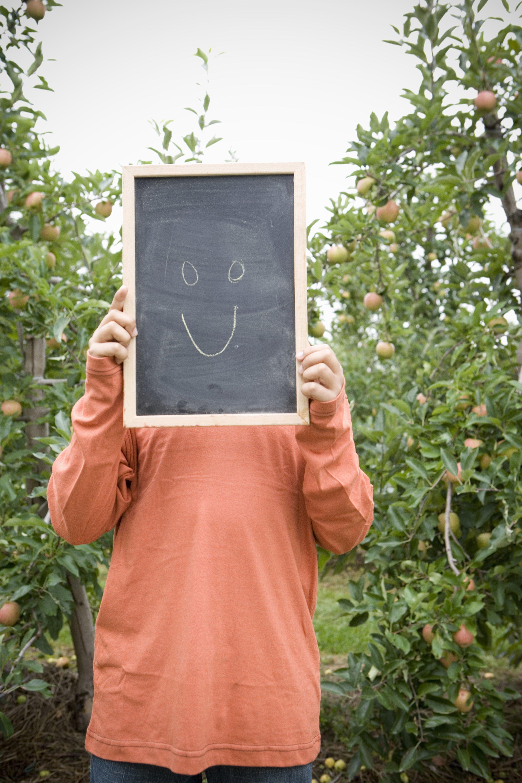 Boy on Apple Farm holding Chalkboard with Happy Face