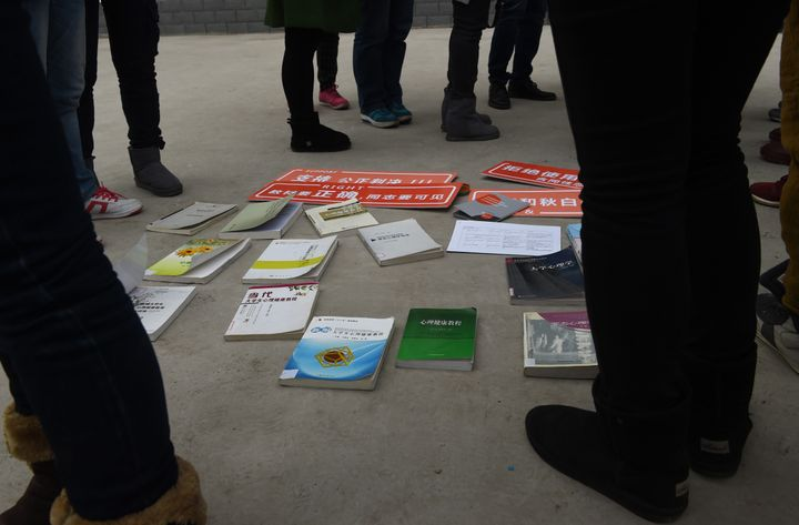 LGBT activists and journalists stand around textbooks they say present being gay as a disease or psychological disorder.