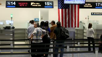 MIAMI, FL - MARCH 04: International travelers wait in line to speak with a CBP officer as they arrive at Miami International Airport on March 4, 2015 in Miami, Florida. Miami-Dade Aviation Department and U.S. Customs and Border Protection (CBP) unveiled a new mobile app for expedited passport and customs screening. The app for iOS and Android devices allows U.S. citizens and some Canadian citizens to enter and submit their passport and customs declaration information using their smartphone or tablet and to help avoid the long waits in the exit lanes.  (Photo by Joe Raedle/Getty Images)