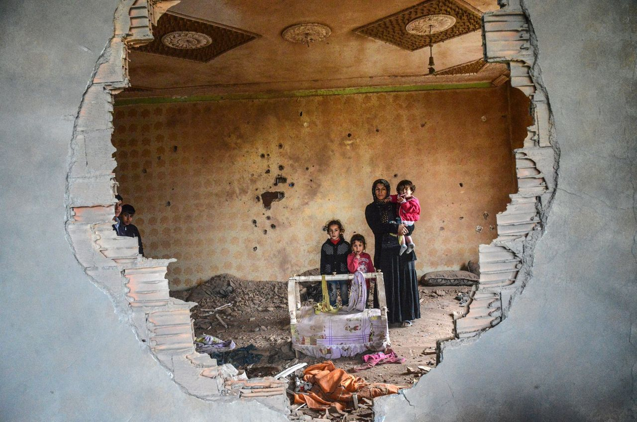 A woman and her children stand in the ruins of a house in the Kurdish town of Silopi on Jan. 19. Turkish forces are fighting to rout a youth militia that is entrenched in several areas of southeast Turkey.