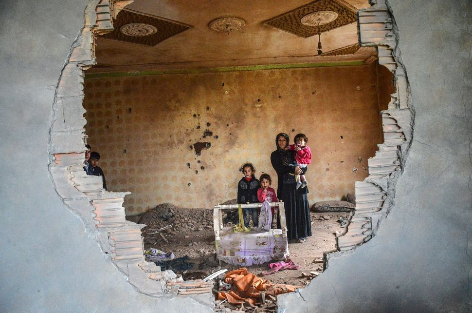 A woman and her children stand in the ruins of ahouse in the Kurdish town of Silopi on Jan. 19. Turkish forces are figh