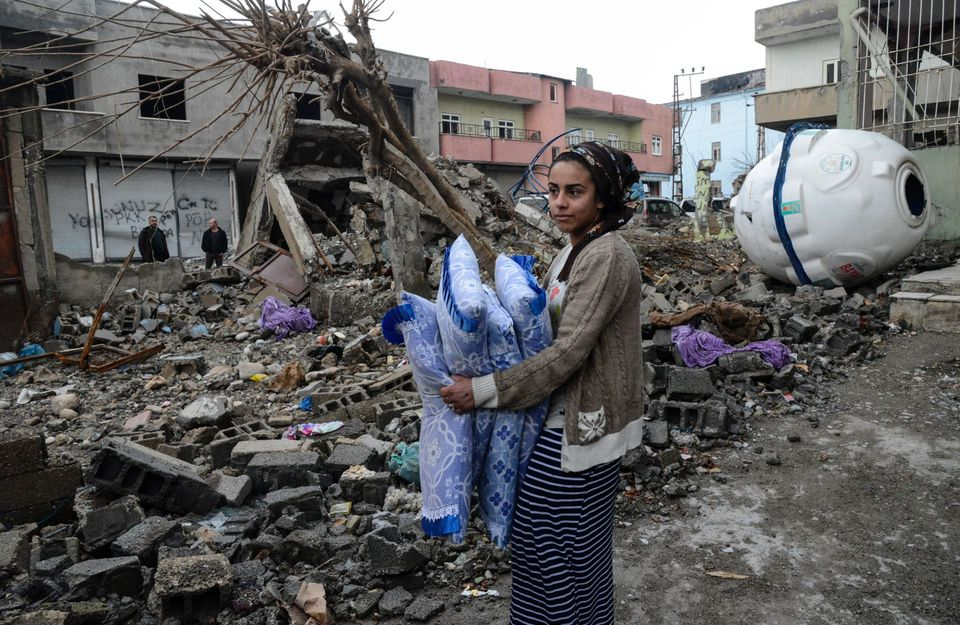 A woman retrieves bedding from the ruins of a house in Silopi. The town was under round-the-clock curfew...