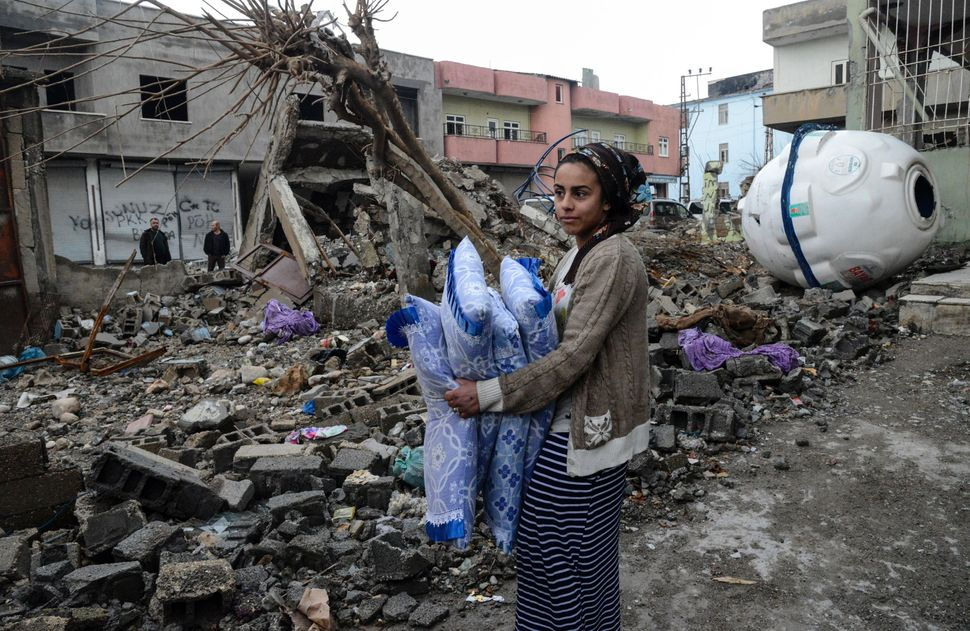 A woman retrieves bedding from the ruins of a house in Silopi. The town was under round-the-clock curfew for 36 days until it