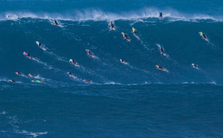 At Waimea Bay, surfers try to paddle over the crest before the powerful wave curls over itself.