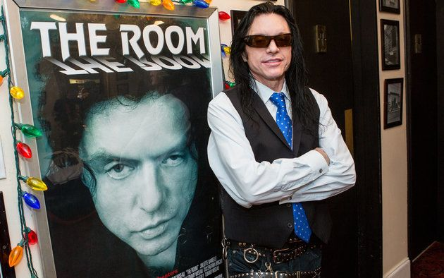 "Tommy Wiseau poses in front of a poster for ""The Room."""