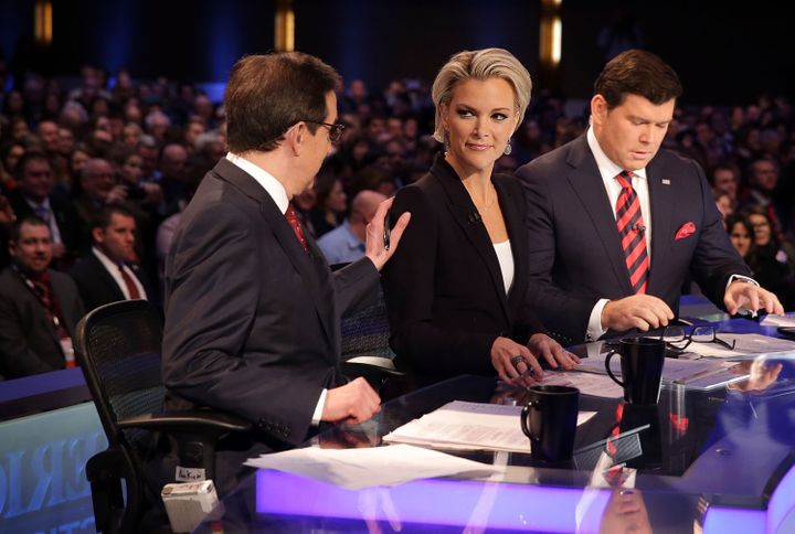 Moderators Chris Wallace (L) pats on the shoulder of Megyn Kelly (2nd L) as they wait with Bret Baier (R) for the beginning o