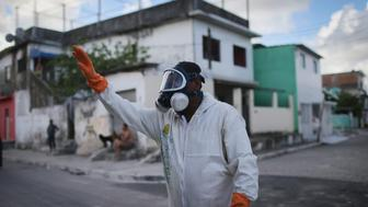 RECIFE, BRAZIL - JANUARY 28:  A health worker calls out to residents to remain inside during fumigation in an attempt to eradicate the mosquito which transmits the Zika virus on January 28, 2016 in Recife, Pernambuco state, Brazil. Two two-man teams were fumigating in the city today. Health officials believe as many as 100,000 people have been exposed to the Zika virus in Recife, although most never develop symptoms. In the last four months, authorities have recorded around 4,000 cases in Brazil in which the mosquito-borne Zika virus may have led to microcephaly in infants. The ailment results in an abnormally small head in newborns and is associated with various disorders including decreased brain development. According to the World Health Organization (WHO), the Zika virus outbreak is likely to spread throughout nearly all the Americas.  (Photo by Mario Tama/Getty Images)