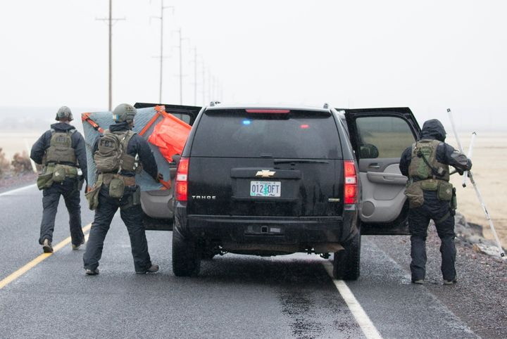 FBI agents remove a road block sign at a checkpoint attheMalheur National Wildlife Refuge in Oregonon Jan.&