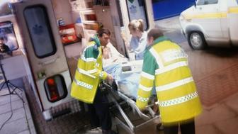 Paramedics lifting injured woman into ambulance (Blurred Motion)