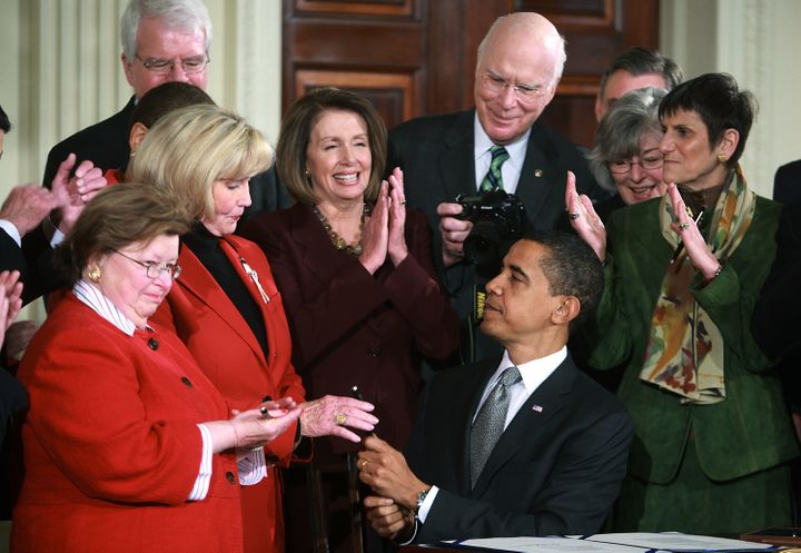 U.S. President Barack Obama (C) hands Lilly Ledbetter a pen after signing the Lilly Ledbetter Fair Pay Act during an event in