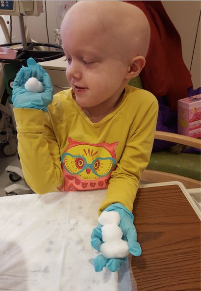 Patient Lucy Wiese playing with snow that Alex Classen brought to the kids.