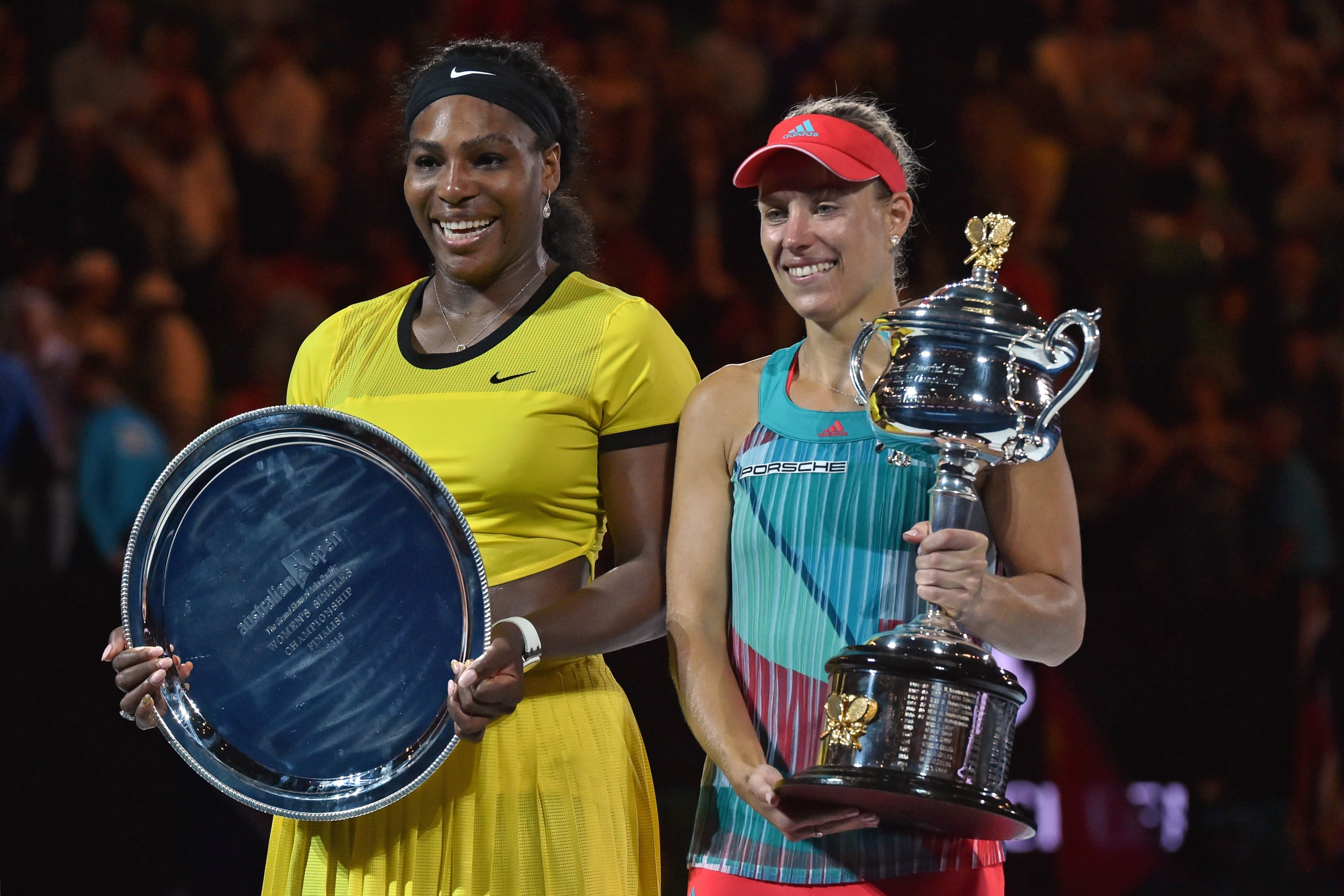 Angelique Kerber of Germany (R) holds the winner's trophy during the awards ceremony following her victory over Serena Williams of the US (L) in their women's singles final match on day 13 of the 2016 Australian Open tennis tournament in Melbourne on January 30, 2016. AFP PHOTO / PAUL CROCK -- IMAGE RESTRICTED TO EDITORIAL USE - STRICTLY NO COMMERCIAL USE / AFP / PAUL CROCK        (Photo credit should read PAUL CROCK/AFP/Getty Images)