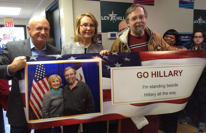 Here's Mark Kelly and Gabby Giffords holding up a banner in support of Hillary Clinton, with a guy whose face is also on the