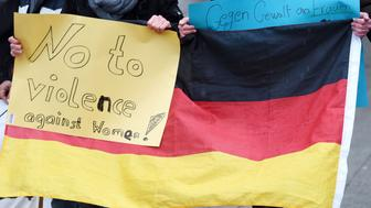 Refugees from Syria hold a sign reading 'No to violence against women' with a German flag as they demonstrate against violence at the Cologne main train station in Cologne, western Germany on January 16, 2016 where violence against women were perpetrated on New Year's Eve.  / AFP / PATRIK STOLLARZ        (Photo credit should read PATRIK STOLLARZ/AFP/Getty Images)
