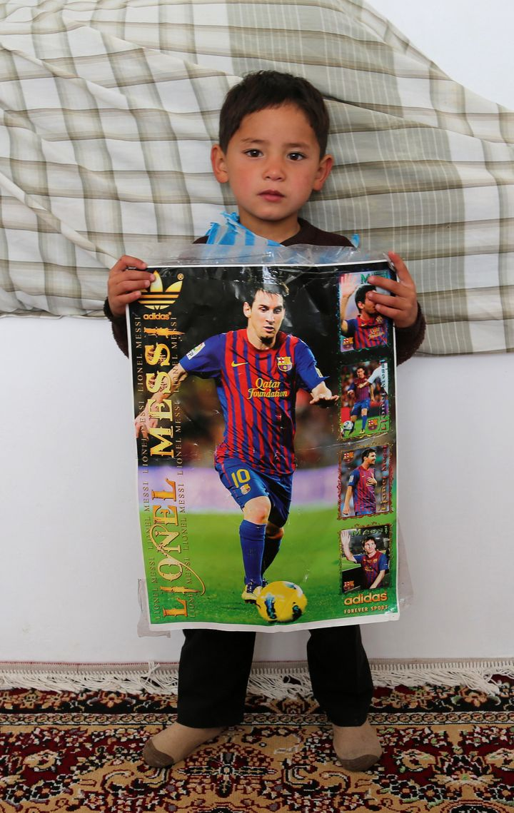 Murtaza wears a plastic bag jersey as he holds a photo of his hero.