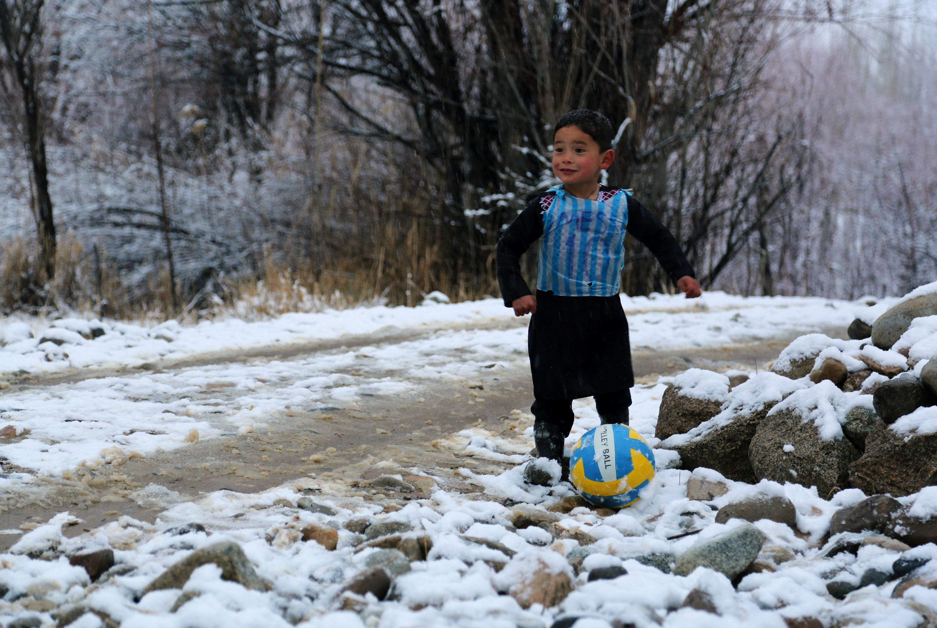 In this photograph taken on January 29, 2016, Afghan boy and Lionel Messi fan Murtaza Ahmadi, 5, wears a plastic bag jersey as he plays football in Jaghori district of Ghazni province.  A five-year-old Afghan boy has become an internet star after pictures went viral of him wearing an Argentina football shirt made out of a plastic bag, complete with his hero Lionel Messi's name. AFP PHOTO / AFP / STR        (Photo credit should read STR/AFP/Getty Images)