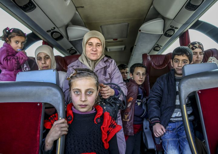 Groups of refugees were transported across the Syrian-Turkish border in buses.