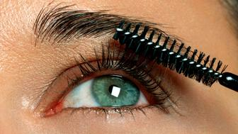 Woman applying eyelash makeup, close-up