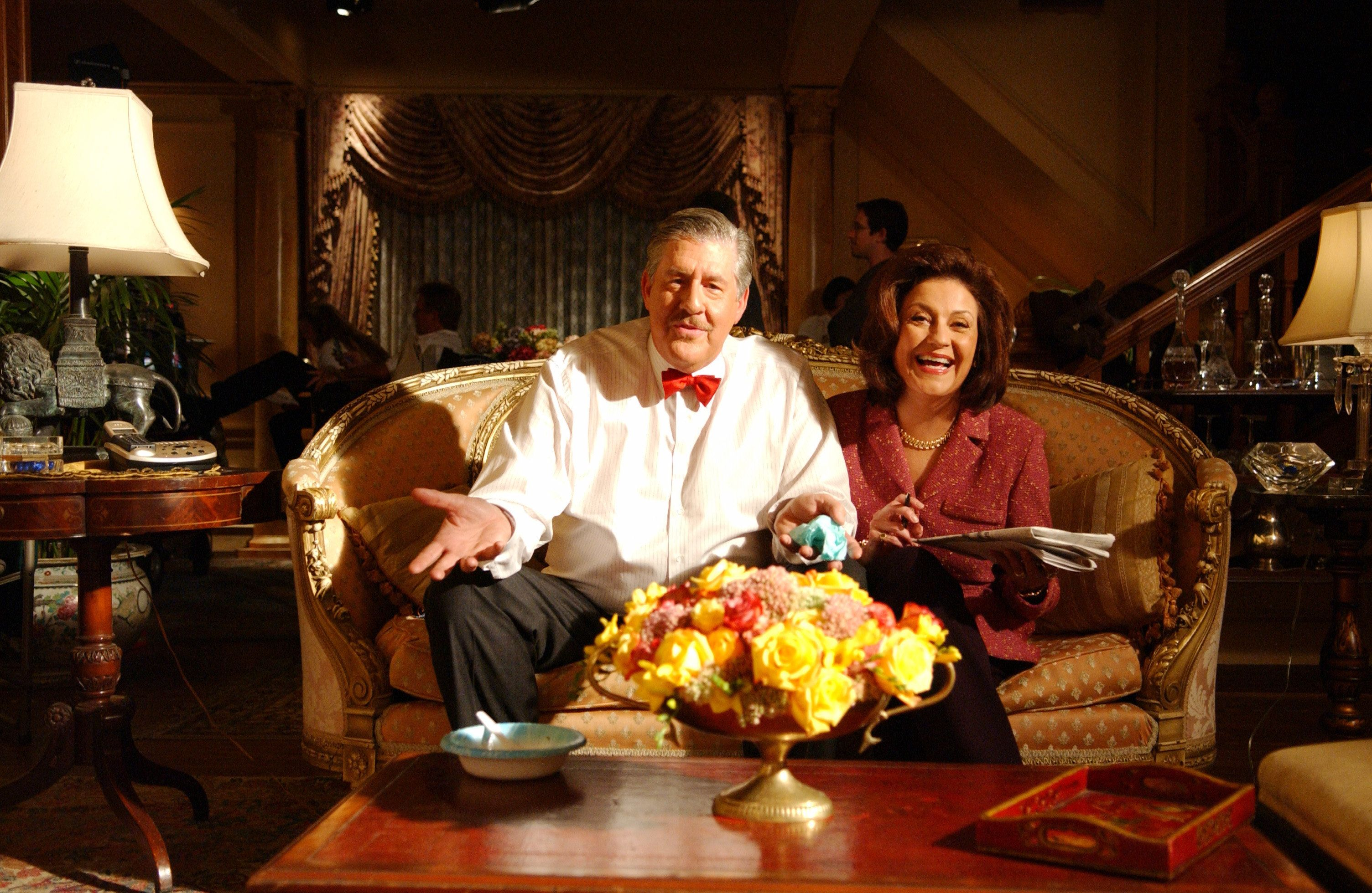 Edward Herrmann as Richard sitting on couch with Kelly Bishop as Emily. (Photo by Patrick Ecclesine/Warner Bros./Getty Images