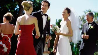 Portrait of a groom and bride shaking hands in a receiving line at a wedding reception