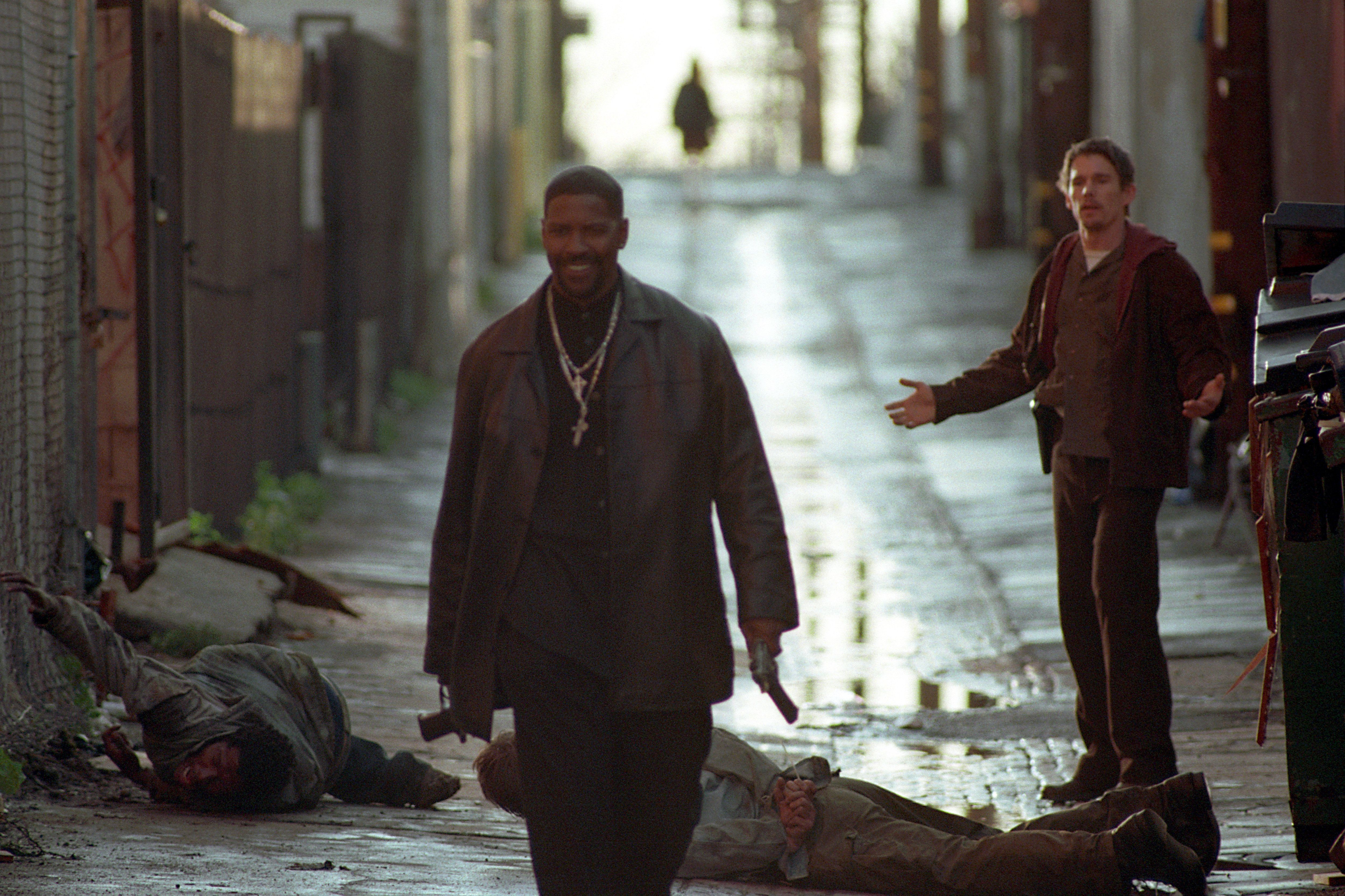 UNSPECIFIED - AUGUST 30:  Full shot in alley of smiling Denzel Washington holding gun/pistol and walking away from Ethan Hawke as Jack Hoyt; Garland Witt as Crackhead _1 (left) and Will Stewart as Crackhead _2 laying on ground.  (Photo by Warner Bros./Getty Images)