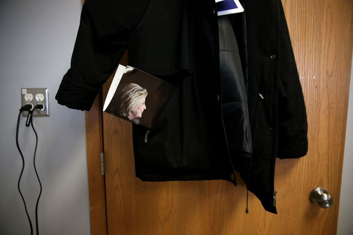 An image of democratic presidential candidate former Secretary of State Hillary Clinton sticks out of a coat pocket that hang