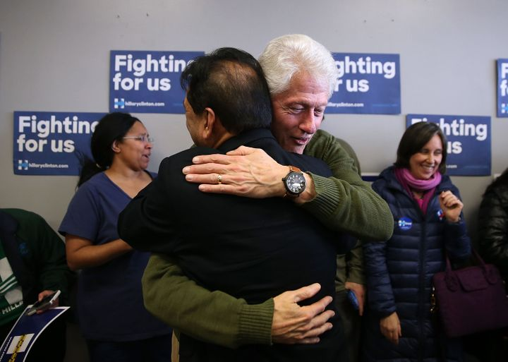 Former U.S. president Bill Clinton hugs a volunteer who is working for his wife, Democratic presidential candidate Hillary Cl