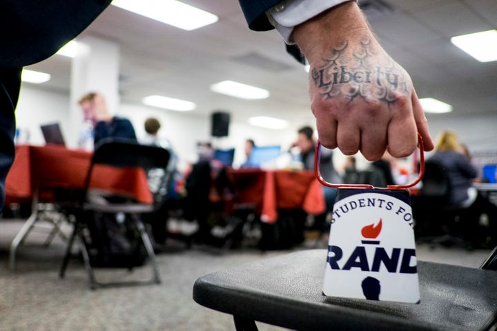 A Rand Paul volunteer rings a cowbell to signify another committed voter for the Republican Kentucky senator at his Des Moine